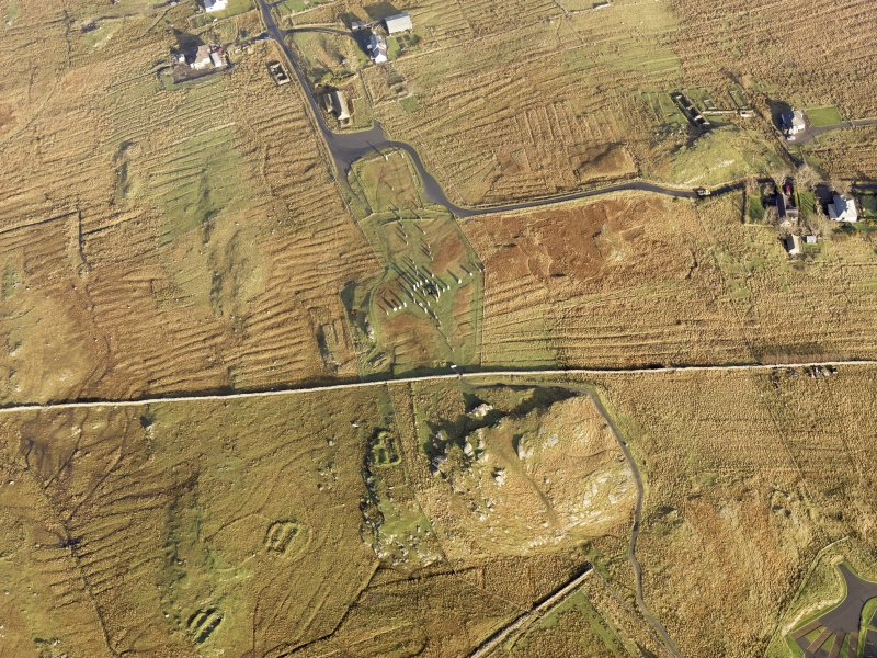 Oblique aerial view centred on the stone circle and stone row, the remains of the buildings and lazy beds at Calanais, taken from the SW.
