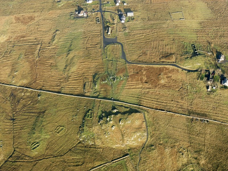 Oblique aerial view centred on the stone circle and stone row, the remains of the buildings and lazy beds at Calanais, taken from the SSW.