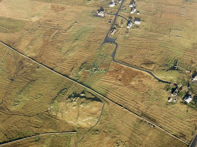 Oblique aerial view centred on the stone circle and stone row, the remains of the buildings and lazy beds at Calanais, taken from the SSE.