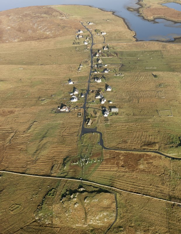 General oblique aerial view centred on the stone circle and stone row, the remains of the buildings and lazy beds at Calanais on the Isle of Lewis, taken from the SSW.