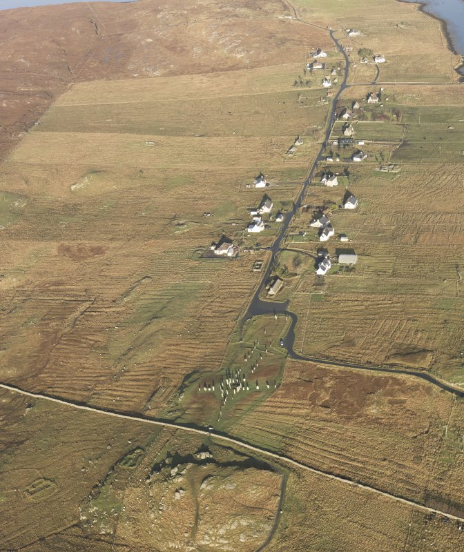 General oblique aerial view centred on the stone circle and stone row, the remains of the buildings and lazy beds at Calanais, taken from the S.