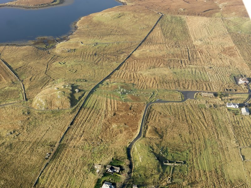 Oblique aerial view centred on the stone circle and stone row, the remains of the buildings and lazy beds at Calanais, taken from the E.