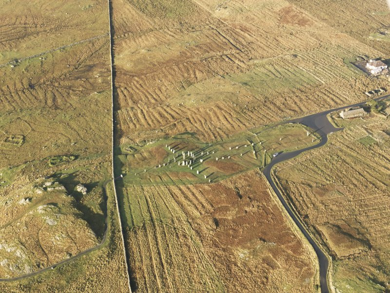 Oblique aerial view centred on the stone circle and stone row, the remains of the buildings and lazy beds at Calanais, taken from the ESE.