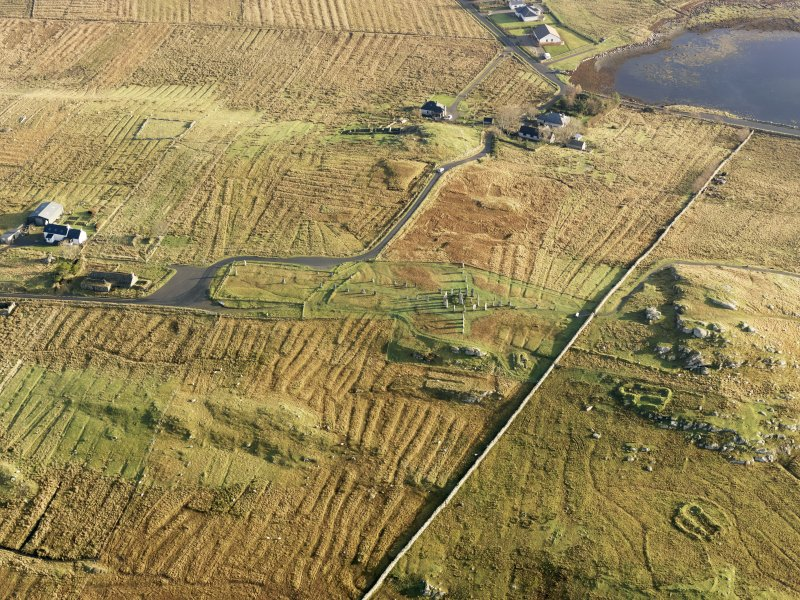 Oblique aerial view centred on the stone circle and stone row, the remains of the buildings and lazy beds at Calanais, taken from the W.