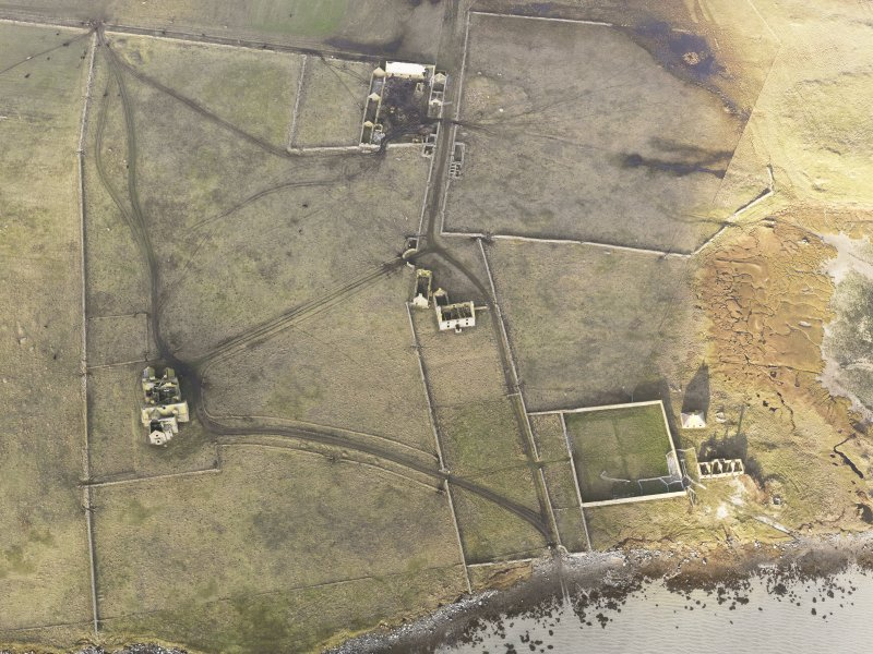 Oblique aerial view of the remains of Vallay House and Old Vallay House, Vallay, North Uist, taken from the SSE.