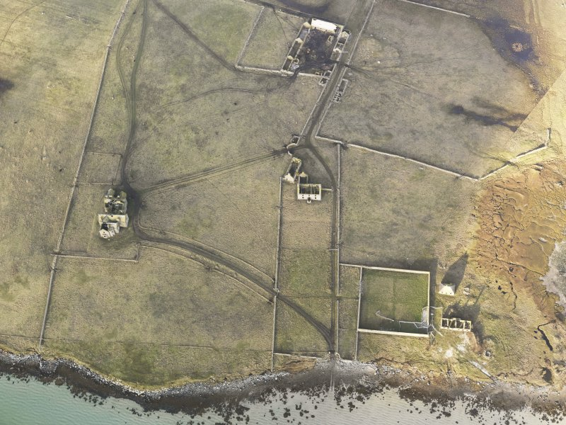 Oblique aerial view of the remains of Vallay House and Old Vallay House, Vallay, North Uist, taken from the SE.