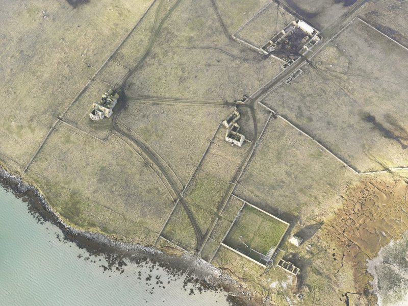 Oblique aerial view of the remains of Vallay House and Old Vallay House, Vallay, North Uist, taken from the ESE.