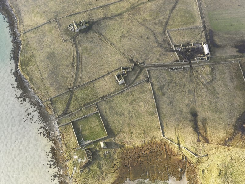 Oblique aerial view of the remains of Vallay House and Old Vallay House, Vallay, North Uist, taken from the E.
