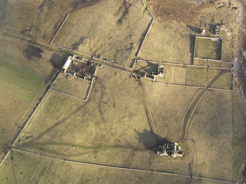 Oblique aerial view of the remains of Vallay House and Old Vallay House, Vallay, North Uist, taken from the SW.