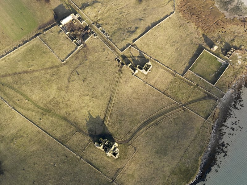 Oblique aerial view of the remains of Vallay House and Old Vallay House, Vallay, North Uist, taken from the SSW.