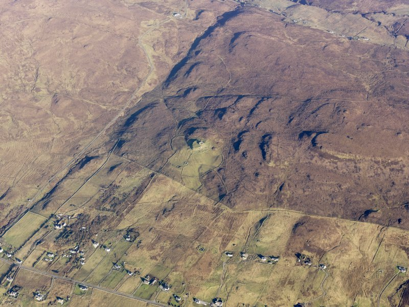Oblique aerial view of the remains of the Dun Hallin broch and the township of Dunhallin, with the remains of the adjacent field system, enclosuires and lazy beds, Waternish, Skye, taken from the SW.