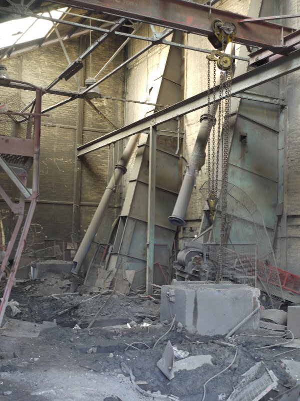 Pan House/ Machine Wing., ground floor. Interior. View from north wast. There were three pan mills on this level. All have been removed prior to demolition. Two of the bucket elevators from the pan mills and supplying the crushed clay hoppers in the adjacent pan house compartment are visible.