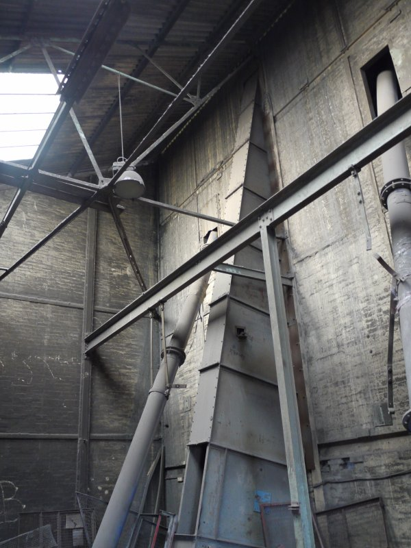 Pan House/ Machine Wing , Ground floor. Interior. View from west showing structure of lower level of pan house. Pan mill no. 3's casing for its bucket conveyor to the screens above, can be seen.