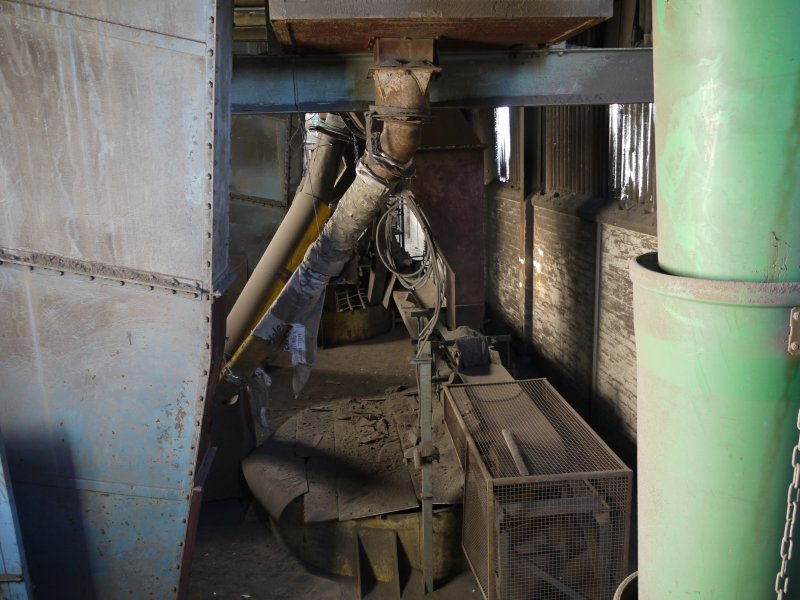 Pan House/ Machine Wing, 1st floor/mezzannine. Interior. View of the area below screen loft (2nd floor/mezzannine). The bucket elevator is on the left and the screened clay to be returned to Pan Mill floor for re-grinding is contained in the pipes. The yellow top of Hopper 2 can be seen.