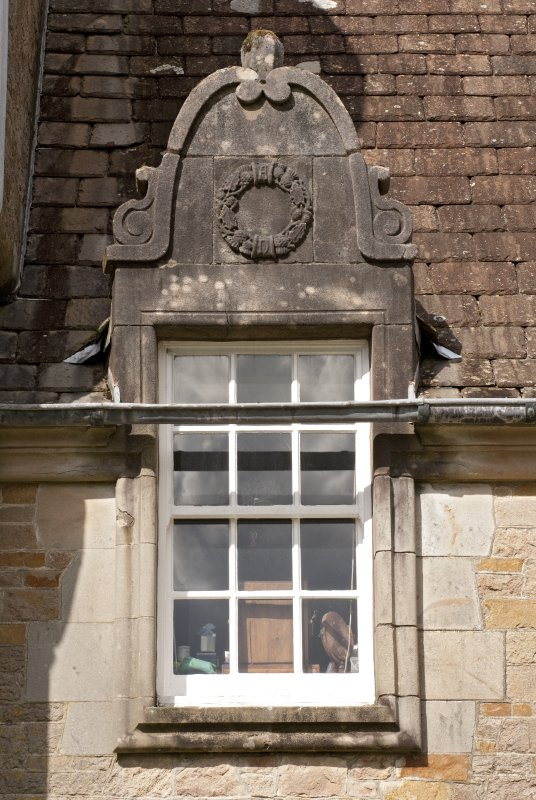Detail of west dormer window with carved stone pediment at 1st floor level of south facade