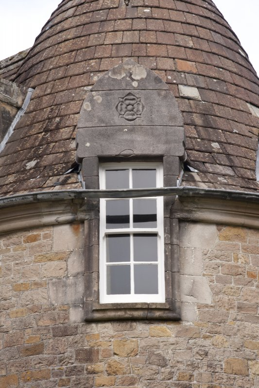 Detail of west dormer window with carved stone pediment at 2nd floor level of south facade