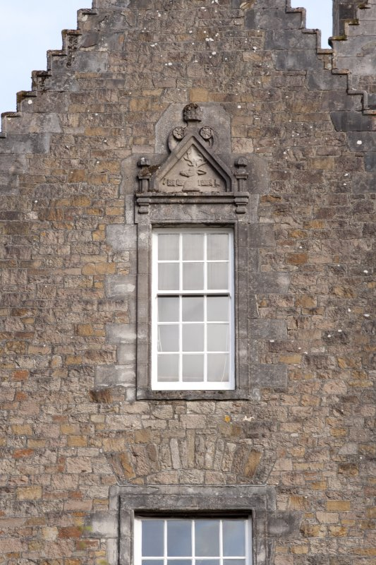 Detail of window with carved stone pediment on north gable of west facade