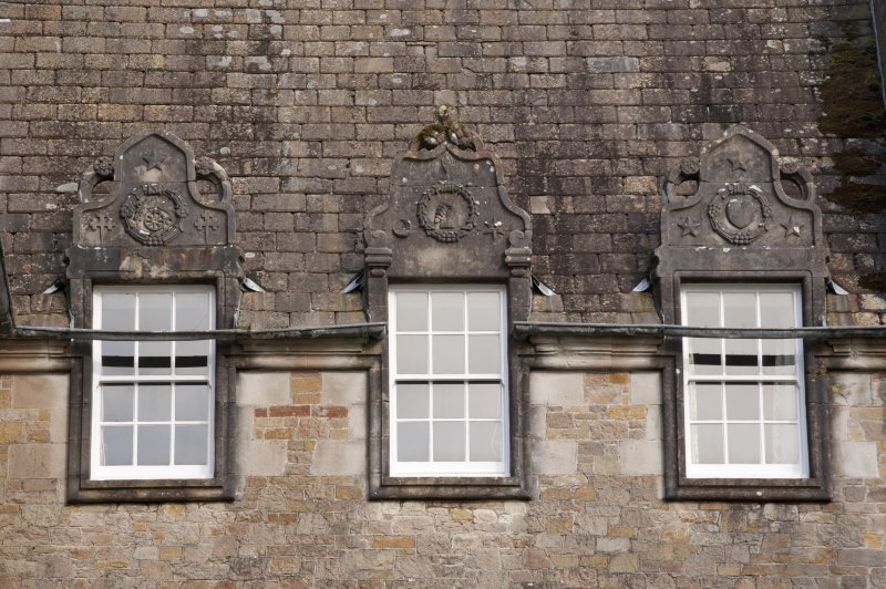 Detail of three dormer windows with carved stone pediments on west facade, Ardkinglas House.