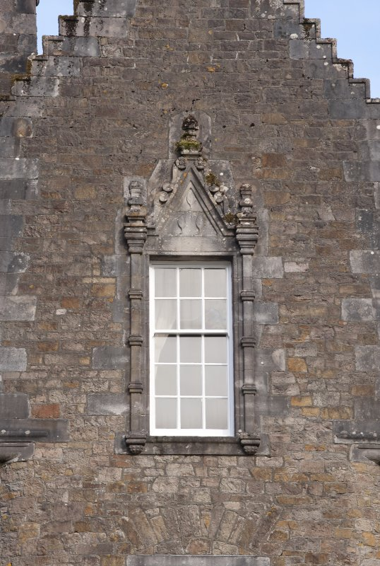 Detail of window with carved stone pediment on south gable of west facade