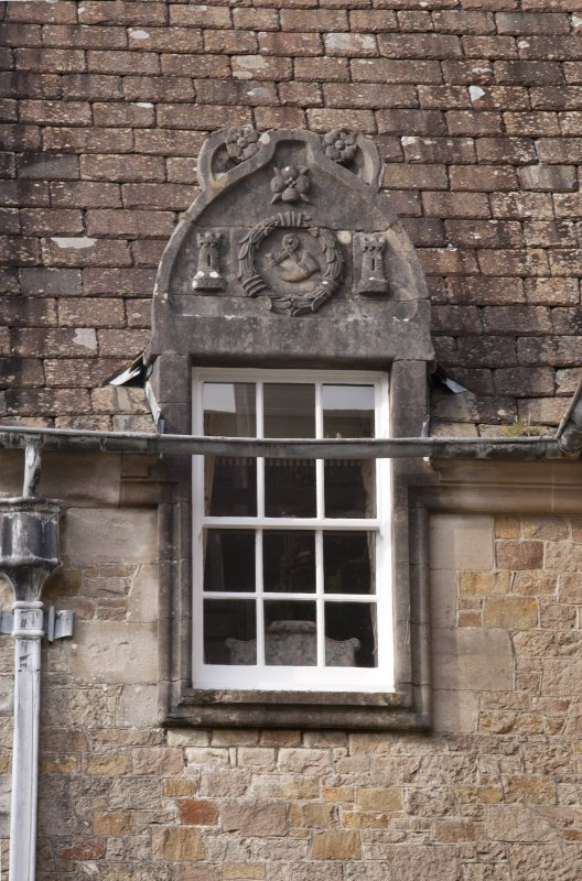 Detail of dormer window with carved stone pediment on south face of north gable of west facade