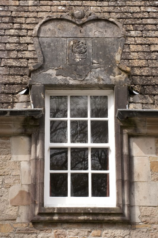 Detail of central dormer window with carved stone pediment at 1st floor level of east facade