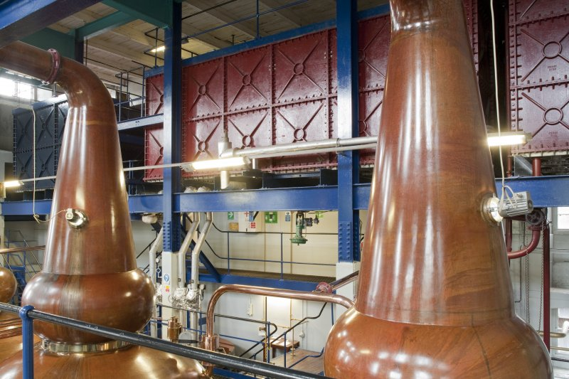 Interior. Still house, view showing storeage tank behind copper stills