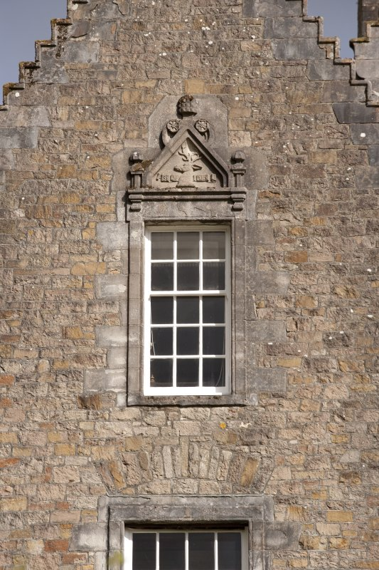 Detail of 2nd floor window with carved stone pediment on north gable of west facade