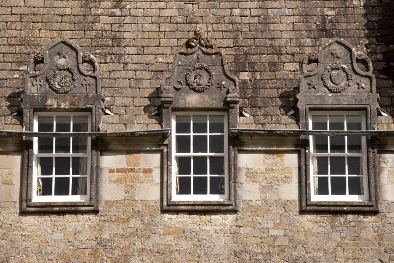 Detail of three dormer windows with carved stone pediments at 2nd floor level of west facade