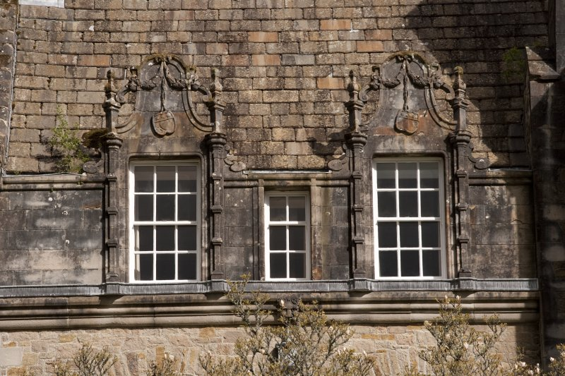 Detail of two dormer windows with carved stone pediments at 2nd floor level of west facade