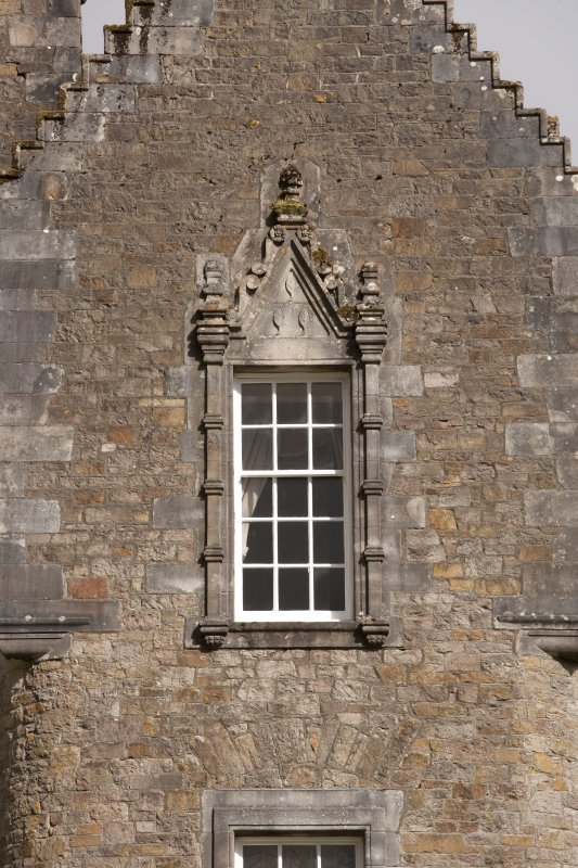 Detail of 2nd floor window with carved stone pediment on south gable of west facade
