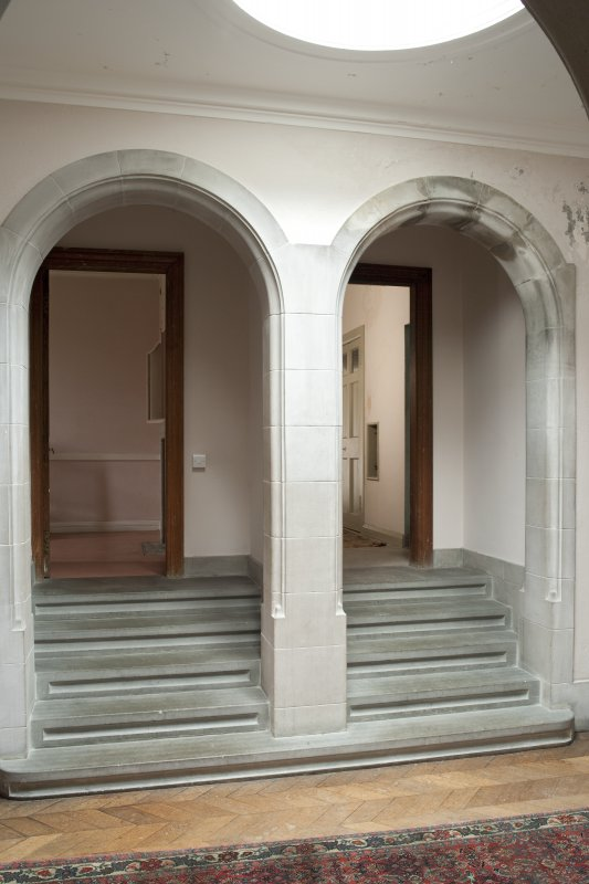 Interior. 2nd floor, corridor, view of double arch and stairs at north end