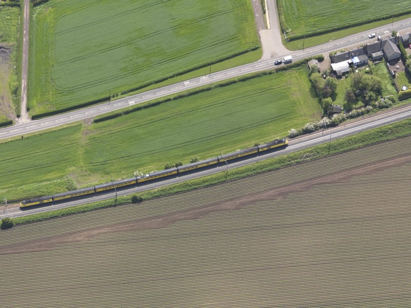 Oblique aerial view of train passing the Ballencrieff estate, taken from the NW.