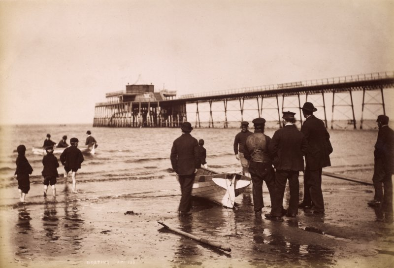 View of men and boat on beach by Portobello pier. Titled: 'Boating. J P. 135'. Subtitled in pencil: 'Portobello Blown down after 1918'. PHOTOGRAPH ALBUM NO.195: PHOTOGRAPHS BY G W WILSON & CO