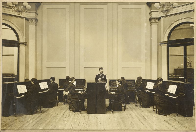 Interior view of The Edinburgh Ladies' College, Edinburgh showing music room.  Titled: 'The Edinburgh Ladies' College. Edinburgh Merchant Company Schools No3'.