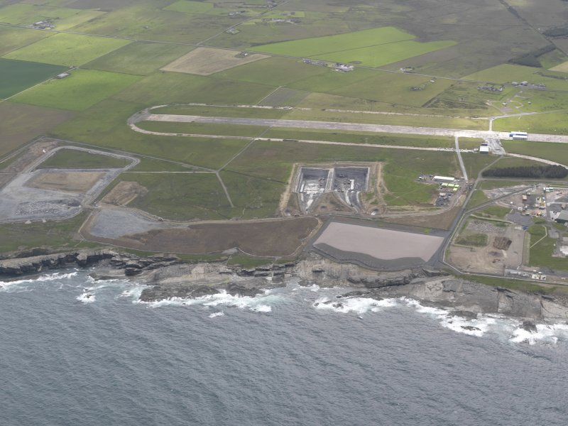 Oblique aerial view of Dounreay Nuclear Development Establishment, centred on the site of the storehouses, looking SE.