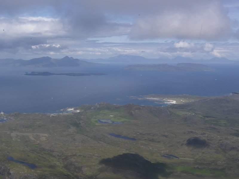 Oblique aerial view of Sanna and Portuairk with Eigg, Muck and Rum beyond, looking N.