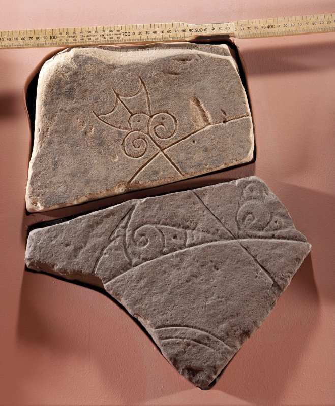View of Pictish symbol stone fragment with replica fragment below (flash), including scale