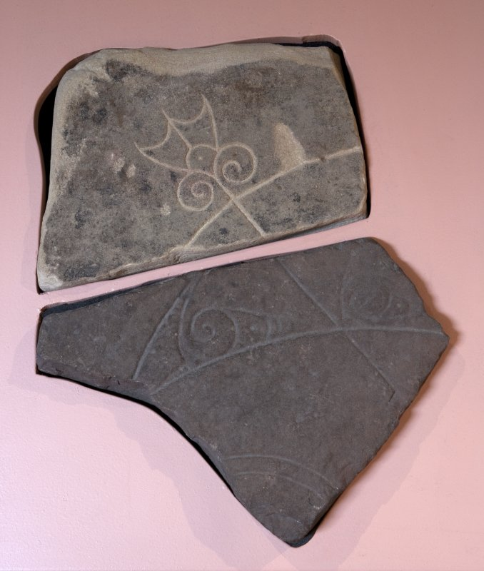 View of Pictish symbol stone fragment with replica fragment below (available light)