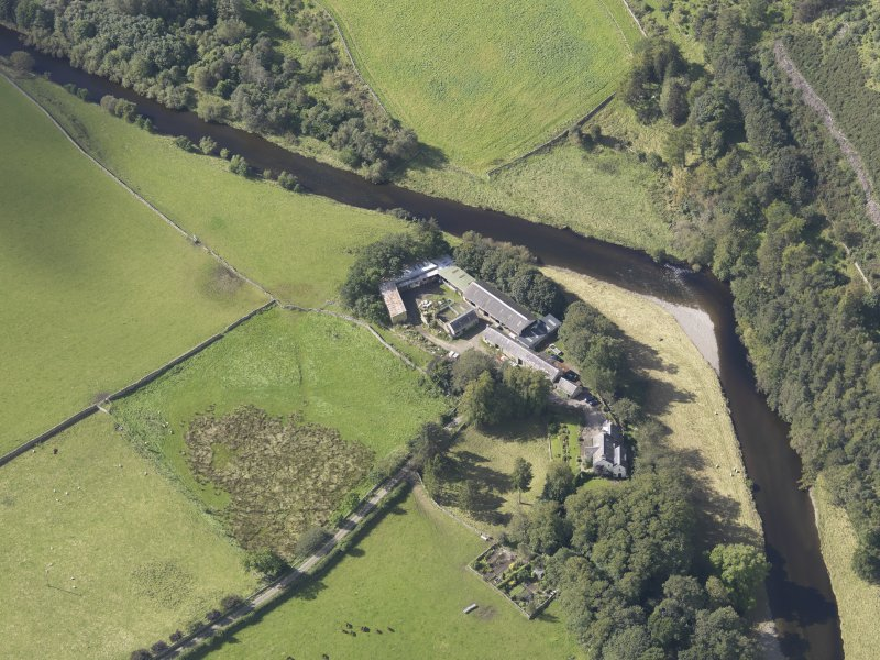 Oblique aerial view of Drumelzier Castle, taken from the NE.