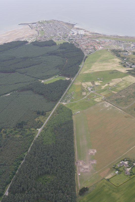 General oblique aerial view of the excavation of the settlement at Clarkly Hill with Burghead beyond, looking WNW.