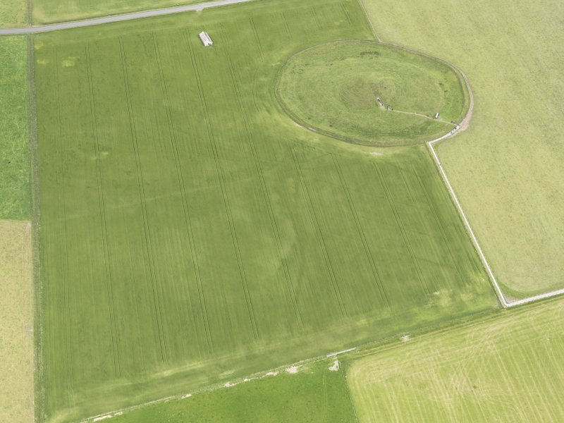 Oblique aerial view of Maeshowe Chambered Cairn, looking NE.