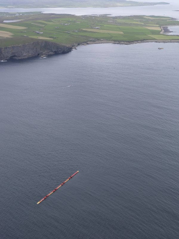 Oblique aerial view of the Pelamis wave energy converter at the European Marine Energy Centre (EMEC), with Stromness beyond, looking SE.