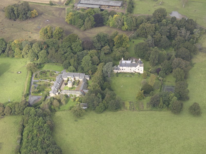 General oblique aerial view of Keith Marischal Country House with adjacent stables, looking to the NW.