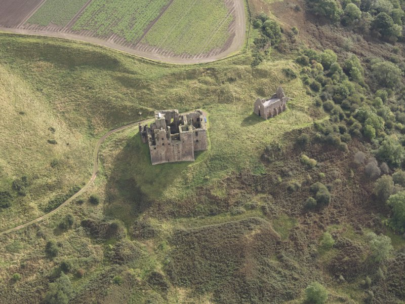 General oblique aerial view of Crichton Castle with The Slaughter House adjacent, looking to the E.