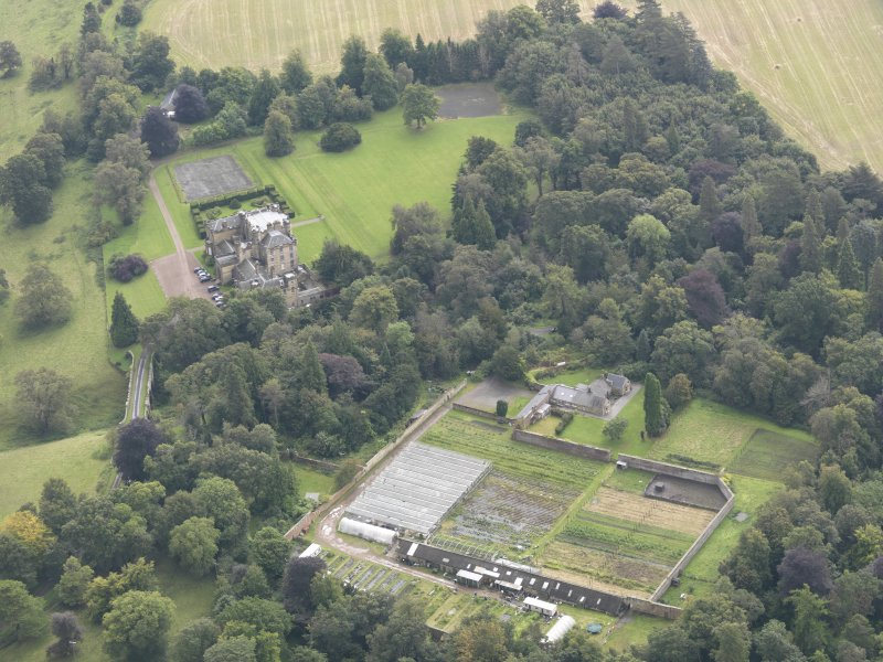 General oblique aerial view of Oxenfoord Castle with adjacent viaduct and walled garden, looking to the SSE.