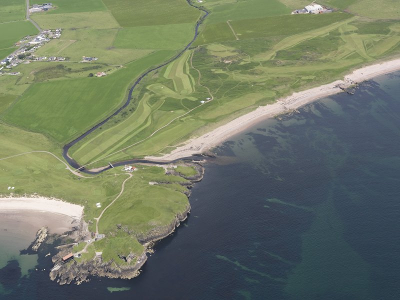 Oblique aerial view of Dunaverty Golf Course, Southend and Brunerican Bay, looking NNE.