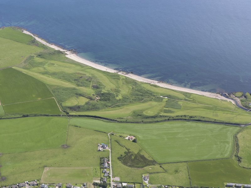 Oblique aerial view of Dunaverty Golf Course, Southend and Brunerican Bay, looking SSW.