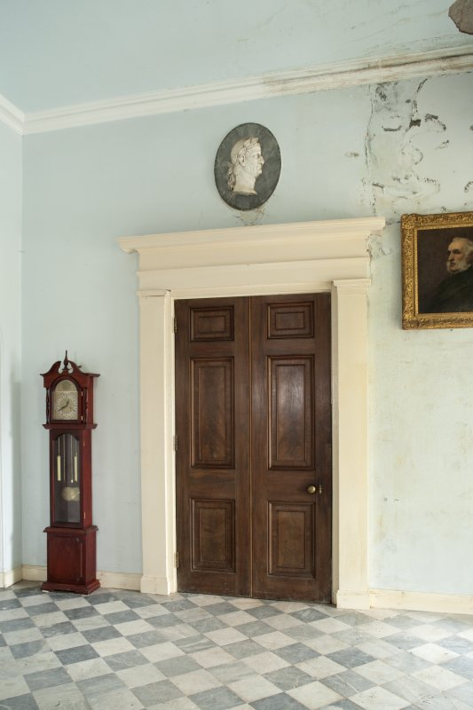 Ground floor. Entrance hall with internal door and wall plaque from west.