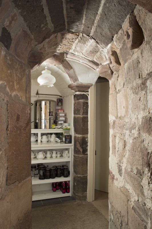 Ground floor. Corridor to east of kitchen, vaulting and carved heads.