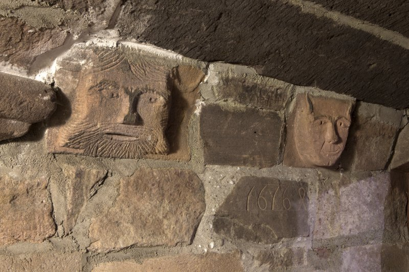 Ground floor. Corridor. Detail of carved heads and datestone.